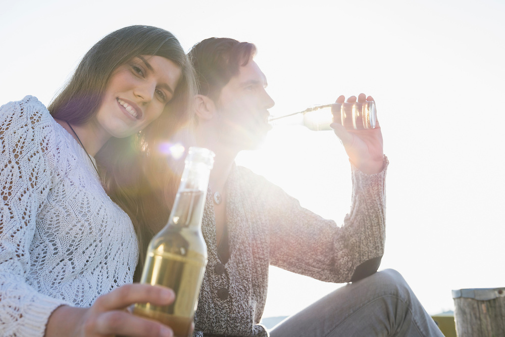Young man woman drinking beer sunset