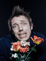 studio portrait on black background of a funny expressive caucasian man offering flowers stressed