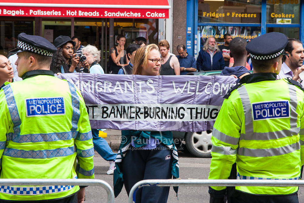 """Cricklewood, London, July 19th 2014. A woman counter-protesting the demonstration by the anti-Islamist """"South East Alliance"""", displays her pro-immigration banner."""