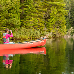 A woman with binoculars in a canoe in Island Pond in Aroostook County, Maine. Deboullie Public Reserve Land.