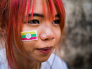 "04 APRIL 2015 - CHIANG MAI, CHIANG MAI, THAILAND:  A Tai (Shan) woman with a Burmese flag on her cheek at the Poi Sang Long Festival in Chiang Mai. The Poi Sang Long Festival (also called Poy Sang Long) is an ordination ceremony for Tai (also and commonly called Shan, though they prefer Tai) boys in the Shan State of Myanmar (Burma) and in Shan communities in western Thailand. Most Tai boys go into the monastery as novice monks at some point between the ages of seven and fourteen. This year seven boys were ordained at the Poi Sang Long ceremony at Wat Pa Pao in Chiang Mai. Poy Song Long is Tai (Shan) for ""Festival of the Jewel (or Crystal) Sons.     PHOTO BY JACK KURTZ"