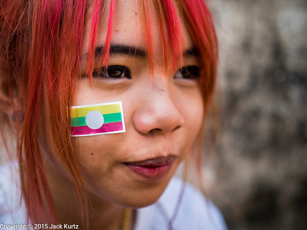 """04 APRIL 2015 - CHIANG MAI, CHIANG MAI, THAILAND:  A Tai (Shan) woman with a Burmese flag on her cheek at the Poi Sang Long Festival in Chiang Mai. The Poi Sang Long Festival (also called Poy Sang Long) is an ordination ceremony for Tai (also and commonly called Shan, though they prefer Tai) boys in the Shan State of Myanmar (Burma) and in Shan communities in western Thailand. Most Tai boys go into the monastery as novice monks at some point between the ages of seven and fourteen. This year seven boys were ordained at the Poi Sang Long ceremony at Wat Pa Pao in Chiang Mai. Poy Song Long is Tai (Shan) for """"Festival of the Jewel (or Crystal) Sons.     PHOTO BY JACK KURTZ"""