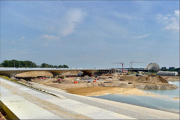 Nederland, Nijmegen, 25-6-2015 De nevengeul aan de overkant van de Waal bij Lent nadert zijn voltooiing. Grootste onderdeel van de vele werken van Rijkswaterstaat om bij hoogwater een betere waterafvoer in de rivier te hebben. Bij de nieuwe recreatiekade. Het is een omvangrijk project waarbij onder meer de pijlers van het spoorviaduct een bredere basis kregen omdat die straks in de loop van het water staan. Ook de n325 die vanaf de Waalbrug naar Arnhem loopt ist over 400 meter opnieuw worden aangelegd omdat het talud vervangen wordt door een nieuwe brug met drie gracieuze pijlers. De brug is afgelopen weekend open gegaan. Het dorp veurlent komt op een kunstmatig eiland te liggen met twee bruggen als ontsluiting. Een voetgangersbrug en een andere, de Promenadebrug, voor normaal verkeer. Inmiddels begint de nieuwe kade aan de noordkant van deze geul vorm te krijgen. Ruimte voor de rivier, water, waal. In de nieuwe dijk wordt een drempel gebouwd die stapsgewijs water doorlaat en bij hoogwater overloopt.The Netherlands, Nijmegen Measures taken by Nijmegen to give the river Waal, Rhine, more space to flow during highwater and to prevent the risk of flooding. Room for the river. Reducing the level, waterlevel. Large project to create a new paralel gully, an extra flow of water, so the river can drain more water during highwater. Due to climate change and expected rise, increase of the sealevel, the Dutch continue to protect their land from the water.Foto: Flip Franssen/Hollandse Hoogte