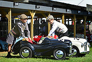 © Licensed to London News Pictures. 14/09/2012. Goodwood, UK Harry Pierly aged 7 (L) cleans his vintage toy J40 pedal car along with brother Jack aged 9. People enjoy the atmosphere at the 2012 Goodwood Revival Meeting today 14 September 2012. Participants are encouraged to dress in period dress.. Photo credit : Stephen Simpson/LNP