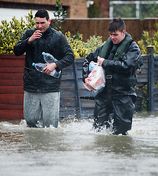 © London News Pictures. 12/02/2014. Egham, UK.  A members of the British Army Royal Engineers (right) helping a resident with his food shopping in Egham, Surrey, which has been hit by heavy flooding. Torrential  rain in the area is due to raise water levels increasing the risk of further flooding. Photo credit : Ben Cawthra/LNP