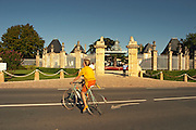 The entrance gate to Chateau Beychevelle in Saint Julien. A cyclist on the road in front