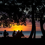 Locals gather for a beer at sunset on Tamarin Beach in Black River. This quiet seaside village has a number of nice guesthouses for tourists that want an experience off the big resorts.