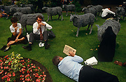 Looking down on office and business workers who are lying down and relaxing in the grass in their lunch break at Finsbury Circus, a circular green park space in the heart of London's financial district, the City of London. Surrounding them is an art instillation of steel sheep that are incongruously grazing among the assorted people, much like they once did when London was a home to livestock en-route to market. In the foreground a man in a dark suit has taken off his jacket and is lying down to complete his Financial Times (FT) crossword. Nearby, a lady and man are sitting eating a packed lunch. The City, is the historic financial core of London from which the modern conurbation grew and its one square mile (2.6 km) boundary has remained constant since the Middle Ages.