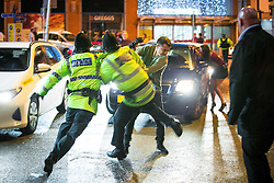 © Licensed to London News Pictures . 01/01/2016 . Manchester , UK . Police attempt to detain a man who has been fighting with another . Revellers in Manchester on a New Year night out at the clubs around the city centre's Printworks venue . Photo credit : Joel Goodman/LNP
