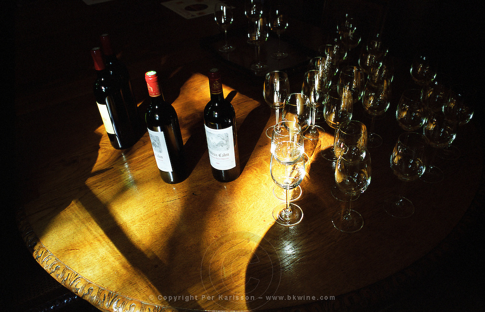 Wine tasting of Chateau Calon in Montagne Saint St Emilion, also owner of Château Corbin-Michotte in St Emilion. Bottles on the wooden table and glasses. Bordeaux Gironde Aquitaine France Europe