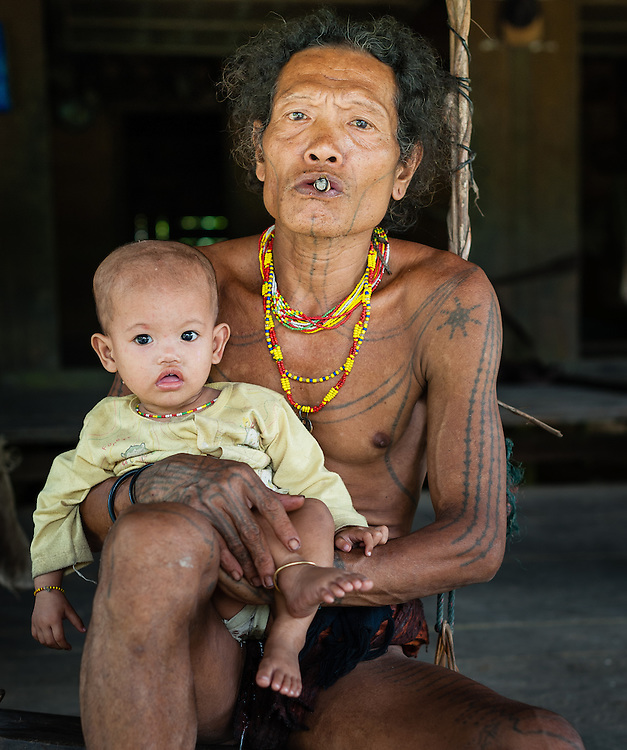 Mentawai indigenous man with baby daughter (Indonesia).
