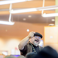 Poet Manuel Gonzales asks guests to snap their fingers before before reciting a poem at the University of New Mexico Zollinger Library in Gallup Thursday.