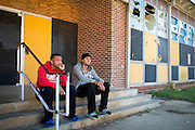 """Kyle Simon and Jessie Cole hang out on the steps of the Grambling State University Natatorium in Grambling, Louisiana on October 23, 2013. The natatorium is boarded up with most windows broken out but plans to renovate the building into a new Health and Wellness Center are """"coming soon.""""   (Cooper Neill for The New York Times)"""
