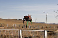 Mongolia. village with communist monument , tractor, on the road to LUN    /  village, ambiance communiste , tracteur a la gloire du kolkhoze, sur la route de Lun   Mongolie