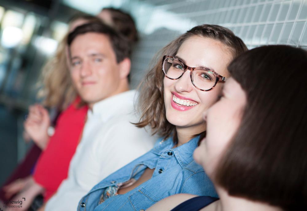 Österreich, Wien, Gruppe junger Leute wartend in U-Bahnstation, an Wand gelehnt, gemeinsam etwas unternehmen, auf dem Weg zu Party, Spaß haben, Sommer,  Freizeit genießen
