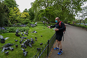 An English man wearing Face Protective Masks who says he walks in throughout St James' Park every day and finds joy in feeding animals is seen feeding ducks, pigeons and squirrels his afternoon walk at St James' Park in London, Britain, on Sunday, May 3, 2020. Britons are now in their sixth week of lockdown due to the Coronavirus pandemic. Countries around the world are taking increased measures to stem the widespread of the SARS-CoV-2 coronavirus which causes the Covid-19 disease. (Photo/ Vudi Xhymshiti)