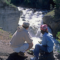 Tourists admire Firehole Falls in Yellowstone National Park, Wyoming