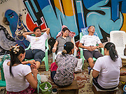 07 APRIL 2013 - CHIANG MAI, CHIANG MAI, THAILAND:  People get massages in front of a wall painted with graffiti during the Chiang Mai Walking Street market.  The Walking Street Market starts at Thapae Gate and runs along the length of Ratchadamnoen Road through the heart of the Old City and has become a Chiang Mai institution. Chiang Mai is the largest town in northern Thailand and is popular with tourists and backpackers.       PHOTO BY JACK KURTZ