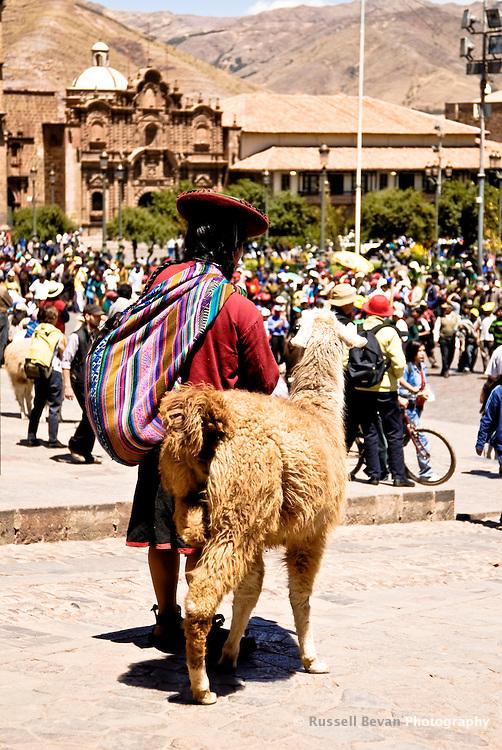 A quechua woman and her llama watch a Protest in Main Square Cusco, Peru