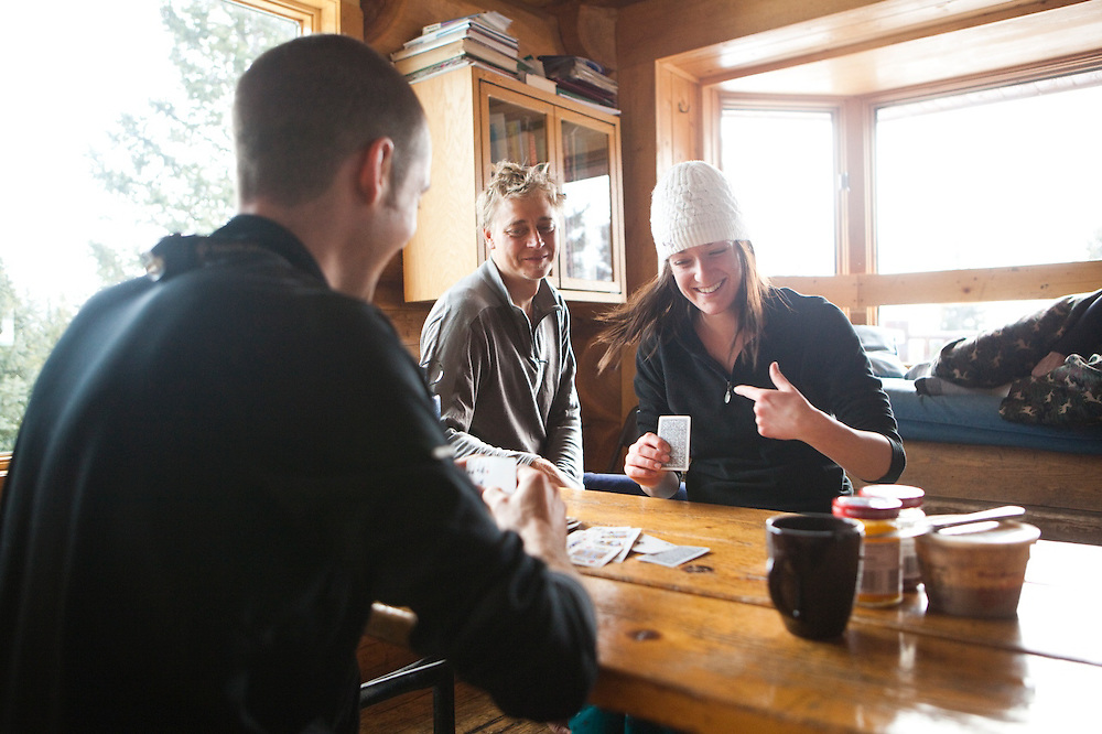 Friends play cards at Francie's Hut, a backcountry cabin in Arapaho National Forest, Colorado.