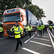 13 local activists locked themselves in specially made arm tubes to block the entrance to Quadrilla's drill site in New Preston Road, July 03 2017, Lancashire, United Kingdom. Police escorting a Quadrilla delivery to the site. The 13 activists included 3 councillors; Julie Brickles, Miranda Cox and Gina Dowding and Nick Danby, Martin Porter, Jeanette Porter,  Michelle Martin, Louise Robinson,<br /> Alana McCullough, Nick Sheldrick, Cath Robinson, Barbara Cookson, Dan Huxley-Blyth. The blockade is a repsonse to the emmidiate drilling for shale gas, fracking, by the fracking company Quadrilla. Lancashire voted against permitting fracking but was over ruled by the conservative central Government. All the activists have been active in the struggle against fracking for years but this is their first direct action of peacefull protesting. Fracking is a highly contested way of extracting gas, it is risky to extract and damaging to the environment and is banned in parts of Europe . Lancashire has in the past experienced earth quakes blamed on fracking.