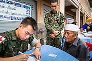 07 JULY 2013 - NARATHIWAT, NARATHIWAT, THAILAND: Royal Thai Marine medics talk to Muslim civilians during a free health screening in Narathiwat. Royal Thai Marines in Narathiwat province held a special ceremony Sunday in advance of Ramadan. They presented widows, orphans and indigent people with extra rice and food as a part of the Thai government's outreach to resolve the Muslim insurgency that has wracked southern Thailand since 2004. The Holy Month of Ramadan starts on about July 9 this year. Muslims are expected to fast from dawn to dusk, engage in extra prayers, recitation of the Quran and perform extra acts of charity during Ramadan. It is the holiest month of the year for Muslims.    PHOTO BY JACK KURTZ