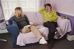 Two residents of women only homeless hostel sitting on sofa in communal lounge talking and eating sandwiches,