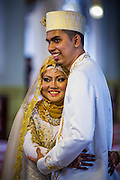 22 DECEMBER 2012 - SINGAPORE, SINGAPORE: A bride and groom pose for guests' photos at the Sultan Mosque in Singapore. The Sultan Mosque is the focal point of the historic Kampong Glam area of Singapore. Also known as Masjid Sultan, it was named for Sultan Hussein Shah. The mosque was originally built in the 1820s. The original structure was demolished in 1924 to make way for the current building, which was completed in 1928. The mosque holds great significance for the Muslim community, and is considered the national mosque of Singapore. It was designated a national monument in 1975.           PHOTO BY JACK KURTZ
