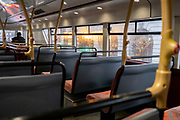 As the government announces the move from Tier 2 to Tier 3 before Christmas, a lone bus pasenger travels on the top deck through Piccadilly during the second wave of the Coronavirus pandemic, on 14th December 2020, in London, England.
