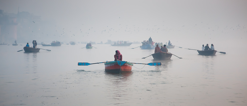 Woman with sari alone on a red boat on the Ganges river at dawn at Varanasi (India)