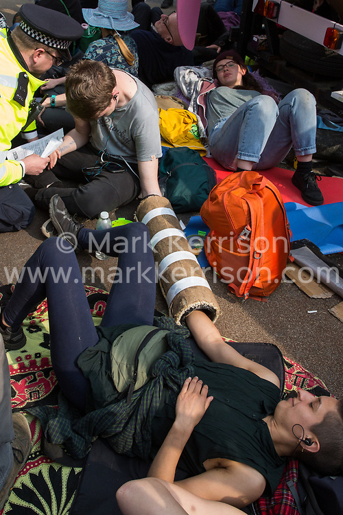 London, UK. 17th April 2019. A police officer speaks to climate change activists from Extinction Rebellion locked onto the Ship of Truth at Oxford Circus as part of International Rebellion activities.