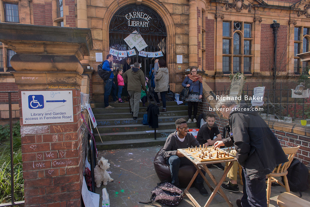 London, UK 2nd April: Campaigners protesting about the closed Carnegie Library play chess outside, in Herne Hill, south London on 2nd April 2016. The angry local community in the south London borough have occupied their important resource for learning and social hub for the weekend. After a long campaign by locals, Lambeth have gone ahead and closed the library's doors for the last time because they say, cuts to their budget mean millions must be saved. A gym will replace the working library and while some of the 20,000 books on shelves will remain, no librarians will be present to administer it. London borough's budget cuts mean four of its 10 libraries will either close, move or be run by volunteers. ©Richard Baker / Alamy Live News.