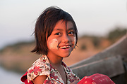 A young girl smiles in a boat along the Ayeyarwaddy River, Aung Zayar Village, Bagan, Myanmar