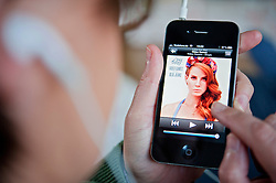Woman listening to music on iTunes app on an iPhone 4G smart phone