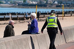Portobello, Scotland, UK. 11 May 2020. Police patrolling promenade and beach at Portobello this afternoon in warm sunny weather. They spoke to the public who were sitting on the beach or on sea wall asking them to keep moving. Pictured; even senior citizens were asked to move. Iain Masterton/Alamy Live News