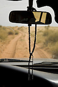 Timbuktu, Mali 2009 - Prayer beads swing from the rearview mirror of our Land Cruiser as the driver works his way along a primitive track between Essakane and Timbuktu.  There are no paved roads in this region of the Sahel and all travel is done in 4 x 4's.
