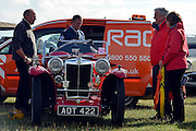 © Licensed to London News Pictures. 15/09/2013. Chichester, UK A  RAC employee in vintage uniform repairs a broken down car. People enjoy the atmosphere at the last day of 2013 Goodwood Revival. The event recreates the glorious days of motor racing and participants are encouraged to dress in period dress. The revival is the only event of its kind to be staged entirely in the nostalgic time capsule of the 1940s, 50s and 60s Photo credit : Stephen Simpson/LNP.