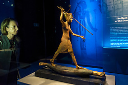 """© Licensed to London News Pictures. 01/11/2019. LONDON, UK. A woman views """"Gilded Wooden Figure of Tutankhamun on a Skiff, Throwing a Harpoon"""".  Preview of """"Tutankhamun, Treasures of the Golden Pharoah"""" at the Saatchi Gallery in Chelsea.  The exhibition celebrates the 100th year anniversary of the opening of Tutankhamun's tomb and displays 150 works in the largest collection of Tutankhamun's treasures ever to leave Egypt.  The show runs 2 November to 3 May 2020.  Photo credit: Stephen Chung/LNP"""