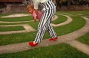 """A mother swings her young child along the pavement and grass of Bath maze Bath Festival Maze (1984) in Beazer Gardens, Riverside Walk, Pulteney Weir, Bath is by renowned maze designer Gilbert Randoll Coate (8 October 1909 – 2 December 2005) who was a British diplomat, maze designer and """"labyrinthologist""""."""