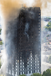 London, June 14th 2017. A fire rages through a residential tower block, Grenfell Tower, in Kensington, West London, with the entire building engulfed in flames. More than 200 firefighters are attending the incident and there are reports of people trapped inside. No figures are available as to casualties. Several flats are still ablaze.