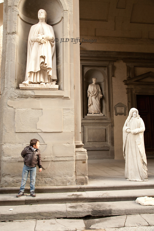 """A living boy looks with, perhaps, suspicion, at a """"living statue"""" in Florence.  Other actual statues in nearby niches."""