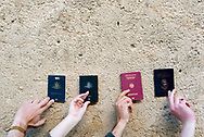 Four travelers -- two from Australia, one from Germany, and one from Argentina -- hold up their passports against a wall