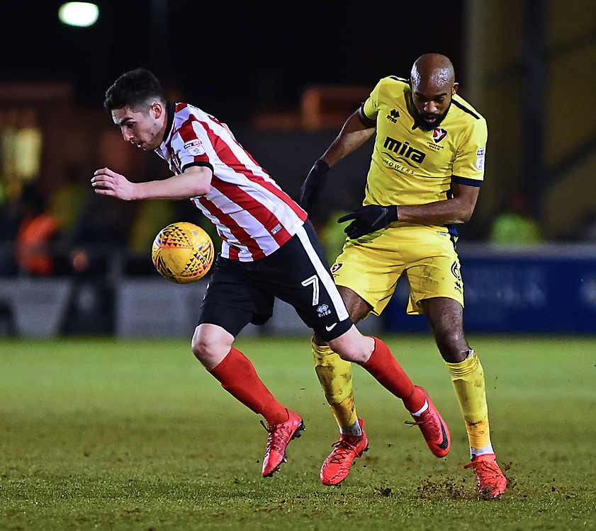 Lincoln City's Tom Pett gets away from Cheltenham Town's Nigel Atangana<br /> <br /> Photographer Andrew Vaughan/CameraSport<br /> <br /> The EFL Sky Bet League Two - Lincoln City v Cheltenham Town - Tuesday 13th February 2018 - Sincil Bank - Lincoln<br /> <br /> World Copyright © 2018 CameraSport. All rights reserved. 43 Linden Ave. Countesthorpe. Leicester. England. LE8 5PG - Tel: +44 (0) 116 277 4147 - admin@camerasport.com - www.camerasport.com