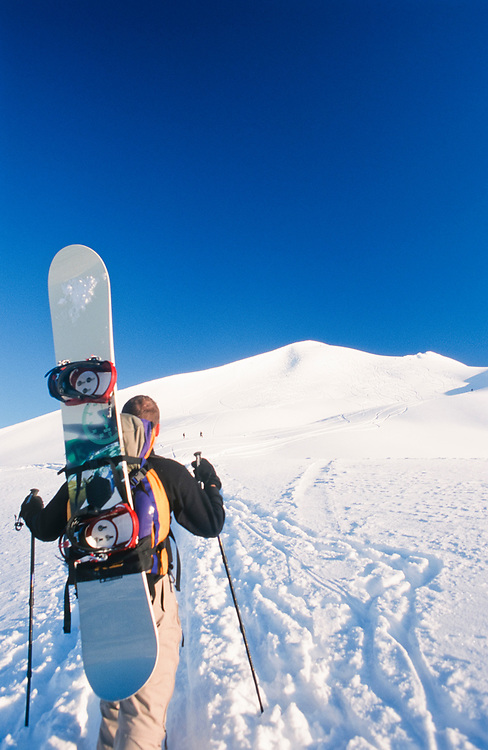 Alaska. Turnagain Pass. Backcountry snowboarders climb the slope they will board down. MR.
