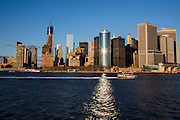 An East River Ferry sails past sun light reflecting off the famous curved facade of 17 State Street building and across the East River in Lower Manhattan, New York City, New York, United States of America.  Lower Manhattan, also known as Downtown Manhattan is the financial, government and cultural district of New York City. <br /> (photo by Andrew Aitchison / In pictures via Getty Images)