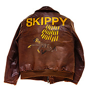 """This type A-2 flight jacket belonged to Joseph F. Doyle, a navigator attached to the 570th squadron of the 390th Bomb Group. Doyle flew 30 missions over Europe as a member of the 570th squadron. On the back of the jacket Doyle painted his crews logo; a German soldier running away from a barrage of bombs. The """"Skippy"""" and her crew flew 30 missions before crashing on their 31st mission, a raid on an airfield in Villacoublay, France, on February 5, 1944. One of the engines on """"Skippy"""" burst into flames just after getting into formation and crossing the English channel. The pilot turned the plane around, and the crew bailed out successfully over the channel as """"Skippy"""" crash landed in England, about 100 yards from the channel."""