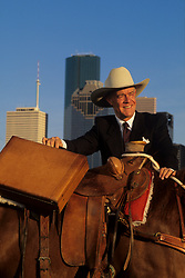 man with briefcase standing by a horse in front of the Houston skyline