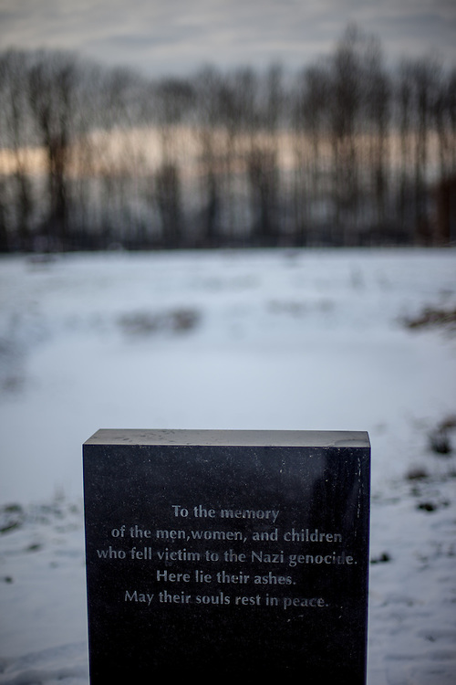 """Memorial stone at the  Auschwitz II/Birkenau camp where lies a pond with 4 gravestones with the inscription in 4 different languages: """"To the memory of the men, women, and children who fell victim to the Nazi genocide. In this pond lie their ashes.  May their souls rest in peace.""""."""