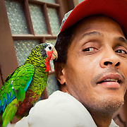 A man and his parrot on the street in Old Havana, Cuba.