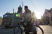 In Amsterdam steekt de man op de fiets de Dam over.<br /> <br /> In Amsterdam a man is crossing the Dam on his bike.